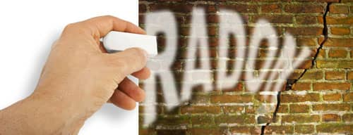 Hand removes radon gas from a cracked brick wall with radon gas escaping